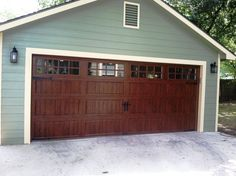 Clopay Gallery Collection grooved panel steel garage door with Ultra-Grain finish. Long panel design with long square windows. Looks like wood without the upkeep. Love how the warmth of the stain color looks against the pale green and creme paint color combo.