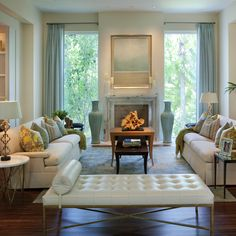 aqua and ivory living room. floor to ceiling windows flanking fireplace instead of typical bookshelves.