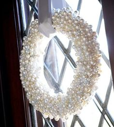 Start with a foam wreath, wrap in white ribbon, and cover with craft store pearls..
