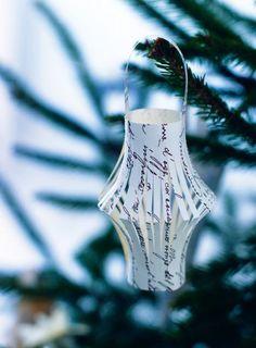 Une lanterne en papier découpée puis pliée comme une décoration de Noël accrochée au sapin