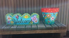Landscaping brick hand painted to welcome friends to your home, along with a matching hand painted floral flower pot.