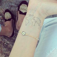 Dainty wrist globe tattoo.
