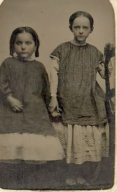 """Pinafores on two little girls. The one on the right appears to be trimmed with one row of """"waved braid"""" (period rick rack) around the neckline and two rows around the sleeves."""