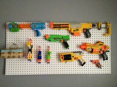 Kids gun rack.  My sister made this for my nephew. Love the idea! Made with peg board and peg hooks with a rubber cover over the tip.