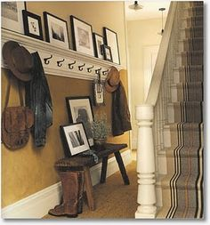 love this entryway idea, lots of hooks and photos leaning again the wall ~This will work in my narrow entry way