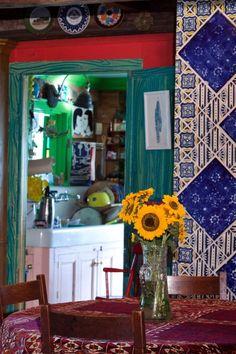 """No espaço destinado às refeições há elementos coloridos como as flores e a toalha de mesa com padrões em vermelho e magenta. Porém, o destaque é o simulacro de madeira feito em verde para o batente da porta e a aplicação de cerâmicas no revestimento do duto da chaminé. Tais azulejos foram um presente de Ann Agee, um artista que participou da mostra """"Bad Girls"""" juntamente com Portia Munson, no início dos anos 1990"""