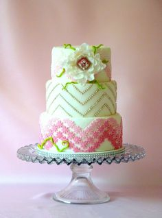 White tiered fondant with ruffled flower and pink ombre flower chevron - Ombre flower chevron pattern on the bottom and top tiers, middle tier chevron style lines (silver dragees). Flower made with 4 different size square cutters to match the pattern. I added green details at the last moment as it looked a bit plain. TFL!