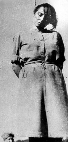"""Jenny-Wanda Barkmann, 24, female guard at the Stutthof concentration camp, hangs from the neck after being executed for atrocities during her """"career."""" She and several others were hanged near Danzig on 4 July 1946. Barkmann brutalized female prisoners viciously and selected women and children for the gas chamber."""