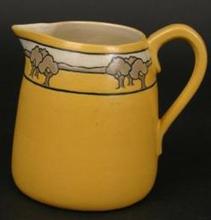 "Circa 1913 signed SEG (Saturday Evening Girls) pottery creamer, yellow ground with landscape band, 5""h, artist initialed 'FL'."