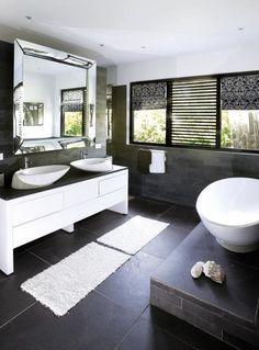 Badkamer met ronde wastafels en bad. Donkere kleuren en natuurstenen ...