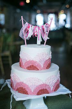 pink scalloped cake with ribbon bunting, photo by Sarah Becker Photography http://ruffledblog.com/notwedding-new-orleans #weddingcake #cakes