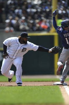 Tigers first baseman Prince Fielder tries to tag out Michael Young in the first inning after catching a high throw from Brandon Inge. (Elizabeth Conley/The Detroit News)
