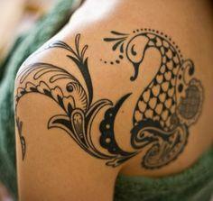 black tribal peacock tattoo on shoulder. http://blog.tattoodo.com/2014/04/40-enticing-peacock-tattoos/