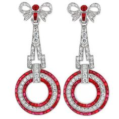 These gorgeous one of a kind earrings feature one hundred twenty-six diamonds with a total weight of 3 carats and one hundred and four rubies that have a total weight of 3 carats. Small ruby and diamond bows adorn the top of these exquisite earrings. Stunning classic Art Deco discs dramatically dangle making these earrings truly exquisite works of art. 1930s.