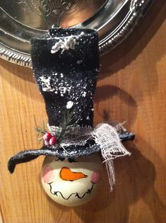 A light bulb painted snowman with a felt hat