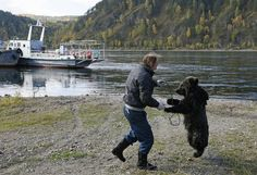 Alexander Kharatokin plays with a 9-month-old brown bear named Masha on the banks of the Yenisei River outside Krasnoyarsk, Siberia, September 19, 2014. Kharatokin, a homeless man and a watchman of a mooring, lives in a wooden hovel near the river. Under the permission of his employer, Kharatokin adopted the orphan bear that was found this spring. He plans to continue living with the bear, whom will be moved to a new larger enclosure after it is constructed. (Photo by Ilya Naymushin/Reuters)