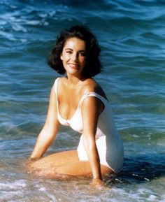 An iconic shot of Elizabeth Taylor splashing in the ocean, from the set of Suddenly Last Summer (1959).