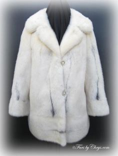 SOLD! Vintage Cross Mink Jacket #CM697; Very Good Condition; Size range: 8 - 12 Misses or Petite. This is a stunning extra-fancy vintage genuine natural cross mink fur jacket. The fur is mainly white mink with streaks of black cross mink. It has a Famous-Barr label and features a large notched collar, banded sleeve ends with a back slit at the sleeve end for interest, and a horizontal band at the bottom hem. It closes with faux mother of pearl buttons outlined with rhinestones. Heavenly!