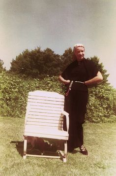 Edie Beale poses with a lawn-chair in the yard of Grey Gardens, using Spot's dog leash as a belt. | c. late-1950s