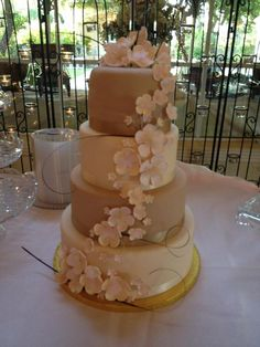 Delicate hand made gum paste flowers made by Taylor Smith, on this beautiful wedding cake from Sassy's Cafe and Bakery!  The neutral color is is just perfect for a timeless wedding cake. The smooth finish with ribbon is on all four tiers. #dreamwedding