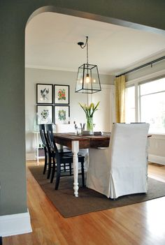 Dining Room Love: paint color in here is Quill by Olympic, yellow curtains, black curtain rod, wood table, black chairs, frames, light fixture