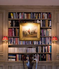 Built-in bookcase with nice lighting - over art & red-shaded sconces