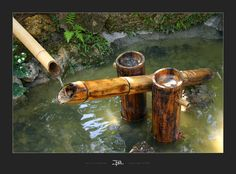 Shishi odoshi. A traditional Japanese way of scaring deer from the garden. The lower pipe fills with water until the balance tips it up spilling the contents. As the pipe tips back it hits a rock making a sound.