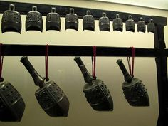 Bell Set.  Shandong Provincial Museum.  These clapperless bells are worked with intricate surface designs.  Although these bells have handles, they are not handle bells. They were suspended from a frame, like the one seen here, and struck on the side to produce the tone.