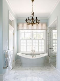 Dream Bath in Blue: Stunning Statement Pieces. An antique French chandelier hung in the center of the room introduces a dark finish that plays off of the marble's natural veining.