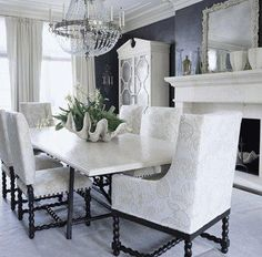 Crystal chandelier, black paint wall color, white & black dining table and chairs, white mirrored secretary and fireplace.