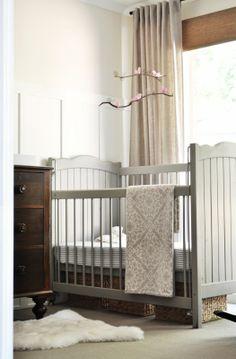 Gray crib, vintage dresser and storage baskets under the crib.