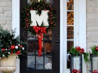 A white monogram wreath pops against this black front door. Black  lanterns filled with red ornaments bring a crisp modern, yet still  traditional, touch to this front porch from  The Yellow Cape Cod.