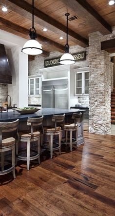 rustic modern kitchen. I love so much about this, from the exposed stone to the awesome chairs.