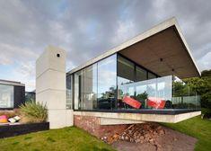 Coastal concrete house on a red sandstone base by ShedKM.