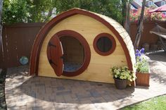 Hobbit Hole Playhouse: outdoor wooden kids playhouse with round front door and windows, live edge cedar roofing, made to order