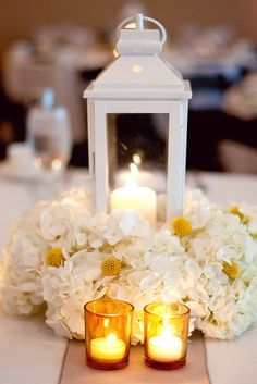 Lantern centerpiece with hydrangea and candle accents.