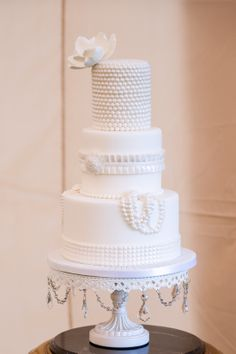 Incredible white wedding cake with sugar flowers and pearls!