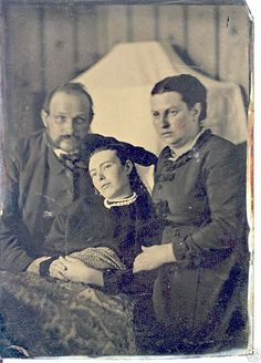 A sadly typical victorian era photo showing a family posed with their now post mortem daughter, it was a custom in that era just before burial, and while it is most sad, yet it is also an understandable custom of that era in time before people could travel great distances in a quick or timely fashion for a loved ones funeral as is possible today, so at least this way ones relatives from afar, could see the beloved deceased person one last time before burial, all via a well posed photograph.