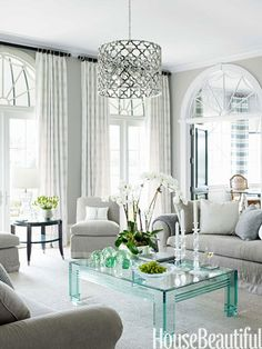 A 1980s Lucite-and-glass table provides a jewellike accent to the muted tones of the living room. Asilah chandelier, Jerry Pair.