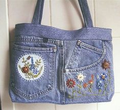Repurposed upcycled jeans into a purse with flowers.