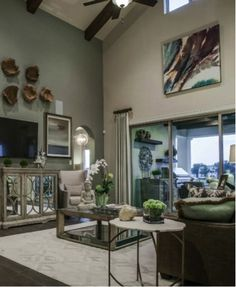 Living room with cathedral ceilings and an elegant color palette of blues and greens. #interior #decor #design #ideas