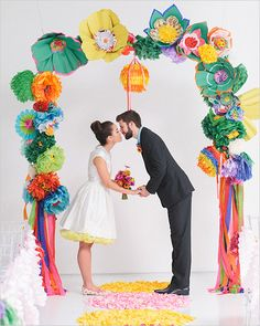 Creating the ideal place for this fun couple to wed, Bows + Arrows crafted an archway in DIY fashion complete with paper flowers, pom-poms, pinwheels, fringe clusters and tassels all in fun, vibrant colors. Showcasing this archway is an aisle runner in geometric shapes with color-blocked petals.