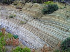 This outcrop consists of visibly layered and grainy rocks but it is not sandstone. This is a pyroclastic rock (volcanic sediment) known as tuff. The outcrop is in France (The Massif Central).