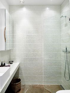 Walk-in glass door shower with mosaic tiles.
