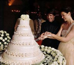 Tom Cruise and Katie Holmes cut into a five-tier wedding cake covered in marzipan roses.
