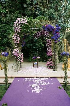 A ceremony altar made of branches is decorated with pink roses and dark purple hydrangeas.