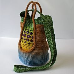 Folk Bag - Spring    A small handbag combining crocheting, knitting and cotton print fabric. Closes with a snap. By paivieerola of   http://peonyandparakeet.blogspot.nl/2010/02/winter-days.html