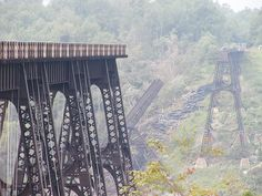 """The Kinzua Bridge was 301 ft tall and 2052 ft long. The bridge was originally built from iron in 1882 and was billed as the """"Eighth Wonder of the World"""", holding the record as the tallest railroad bridge in the world for two years. Before being struck by a tornado and its subsequent collapse in 2003, the Kinzua Bridge was ranked as the fourth-tallest railway bridge in the United States."""