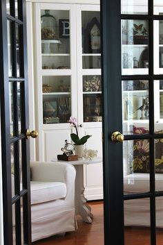 Black French Doors make a nice contrast with the white cabinets & furnishings.
