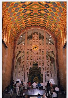 """Guardian Building entrance lobby with two-story Art Deco entrance screen of Monel metal and walls and vaulted ceiling decorated with mosaics and Pewabic Pottery and Rookwood Pottery glazed tiles. The Ezra Winter mural, """"Michigan"""", can be seen in the middle, through the metal grill.  The 1929 Art Deco style Union Trust Building—Guardian Building is located at 500 Griswold Street, Downtown Detroit, Michigan.  Designed by Wirt C. Rowland and built by Gorham Co. of Providence RI (1928-1929)"""
